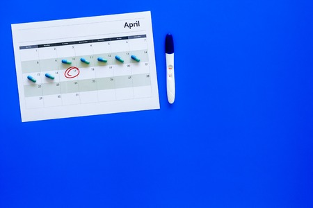 Planning pregnancy. Positive pregnancy test near calendar page and pills on blue background top view copy space Stock Photo
