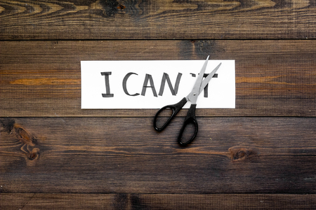 I can concept. Motivate yourself, believe in yourself. Scissors cut the letter t of written word I cant. Dark wooden background top view copy space