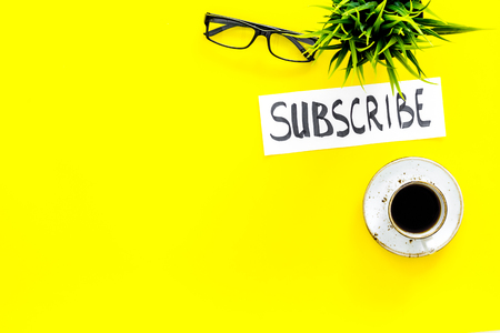Email subscribe concept. Hand lettering subscribe on work desk with plant, glasses, cup of coffee on yellow background top view copy space