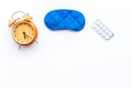 Insomnia concept. Trying to sleep. Help yourself get to sleep. Sleeping pills near sleeping mask and alarm clock on white background top view copy space