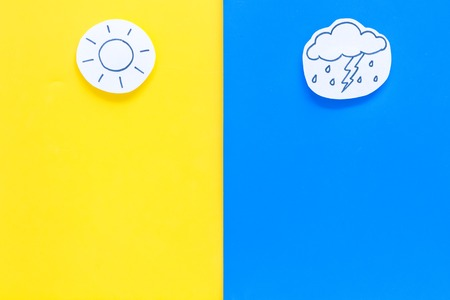 Good and bad weather concept. Template for forecast. Sun vs cloud and lightening with rain on yellow and blue background top view copy space Imagens