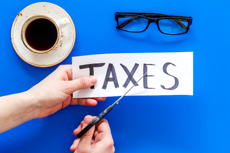 Tax reduce concept. Hands with scissors cut paper with word Taxes on blue background with coffee and glasses top view