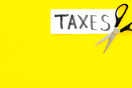 Cut taxes concept. Scissors cut paper with word Taxes on yellow background top view space for text