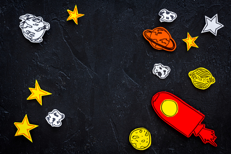 Space tourism concept. Drawn rocket or spaceship near stars, planets, asteroids on black background top view copy space