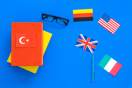 Language study concept. Textbooks or dictionaries of foreign language near flags on blue background top view copy space Stock Photo
