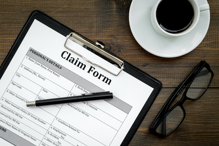 Claim form to fill out on dark wooden desk top view closeup