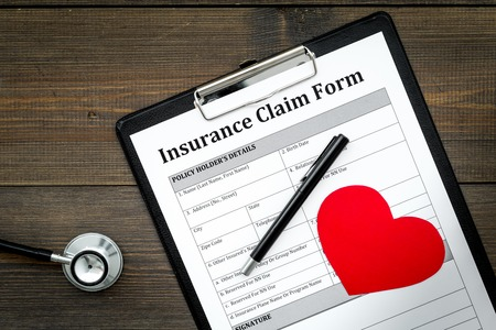 Health insurance claim form for fill out. Empty form near heart sign and stethoscope on dark wooden background top view copy space