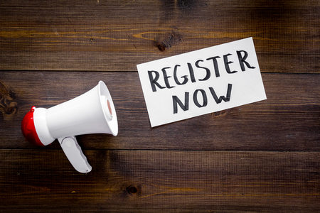 Register now hand lettering icon near megaphone on dark wooden background top view copy space