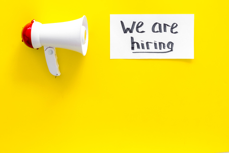 Job recruiting advertisement. We are hiring lettering near megaphone on yellow background top view copy space