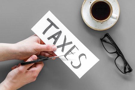 Tax reduce concept. Hands with scissors cut paper with word Taxes on grey background with coffee and glasses top view