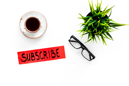 Email subscribe concept. Hand lettering subscribe on work desk with plant, glasses, cup of coffee on white background top view copy space