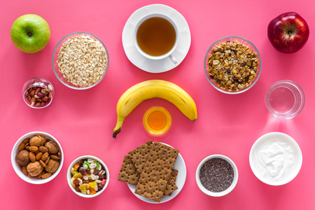 Layout of products for healthy and hearty breakfast. Fruits, oatmeal, yogurt, nuts, crispbreads, chia on pink background top view