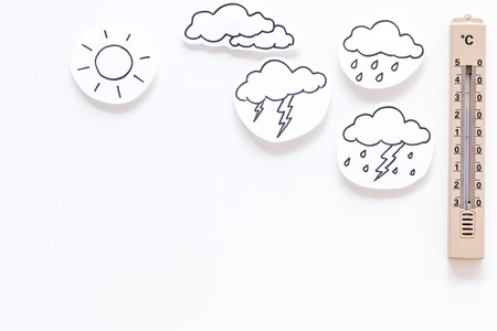 Weather forecast concept. Air temperature. Thermometer among cloud and lightening, sun, rainy clouds on white background top view copy space