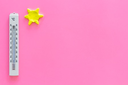 Clear and cloudy weather concept. Air temperature. Thermometer near sun on pink background top view copy space