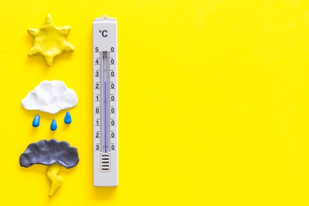 Weather forecast concept. Air temperature. Thermometer among cloud and lightening, sun, rainy clouds on yellow background top view copy space Stock Photo