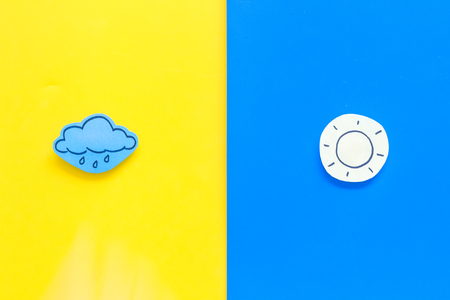 Good and bad weather concept. Template for forecast. Sun vs rainy cloud on yellow and blue background top view copy space