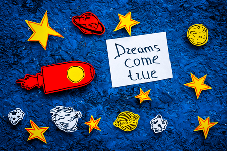Motivational poster. Dreams come true hand lettering at blue cosmos background with rocket and stars top view