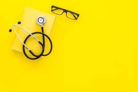 Medical literature. Stethoscope near book and glasses on yellow background top view copy space 写真素材