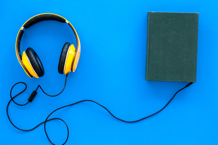 Audiobooks concept. Headphones connected with hardback book with empty cover on blue background top view.