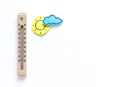Clear weather concept. Air temperature. Thermometer near sun on white background top view.