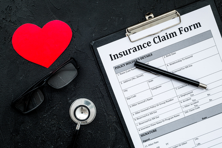 Health insurance claim form for fill out. Empty form near heart sign and stethoscope on black background top view. Stock Photo