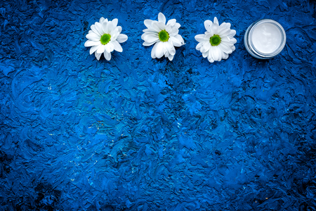 Hypoallergenic baby cream. Chamomile cream in small jar near chamomile flowers on blue background top view.