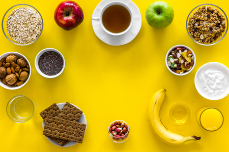Ideas of healthy hearty breakfast for sportsmen. Fruits, oatmeal, yogurt, nuts, crispbreads, chia on yellow background top view. Stock Photo