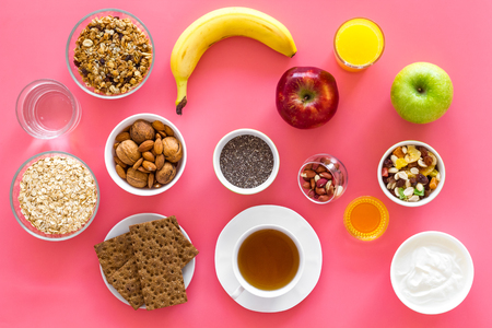 Layout of products for healthy and hearty breakfast. Fruits, oatmeal, yogurt, nuts, crispbreads, chia on pink background top view. Stock Photo