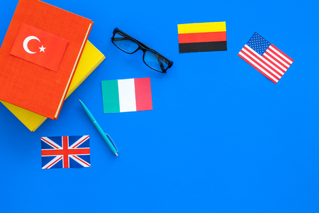 Language study concept. Textbooks or dictionaries of foreign language near flags on blue background top view.