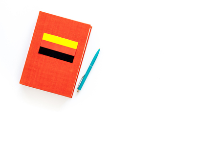 Language study concept. Textbooks or dictionaries of foreign language near German flag on white background top view. Stock Photo