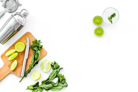 Make mojito cocktail with lime and mint. Shaker, strainer, glass near slices of lime on cutting board on white background top view.