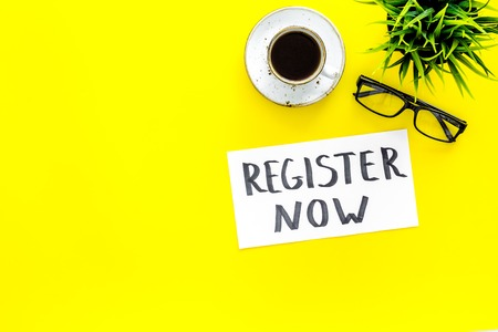 Membership concept. Template for registration. Register now hand lettering icon on word desk with glasses, coffee, plant on yellow background top view.