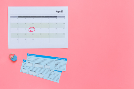 Plan a trip. Buy airplane tickets. Tickets near calendar with date circled on pink background top view. Stock Photo