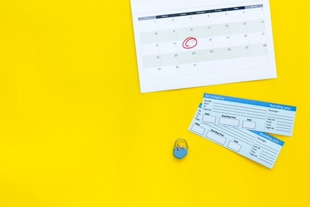 Plan a trip. Buy airplane tickets. Tickets near calendar with date circled on yellow background top view. Stock Photo