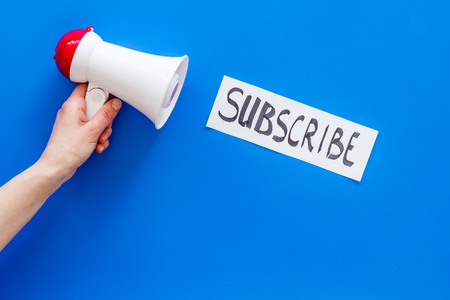Subscribe template or mockup. Hand lettering subscribe near megaphone on blue background top view.