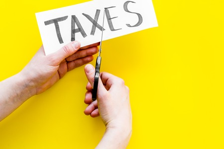 Tax reduce concept. Hands with scissors cut paper with word Taxes on yellow background top view.
