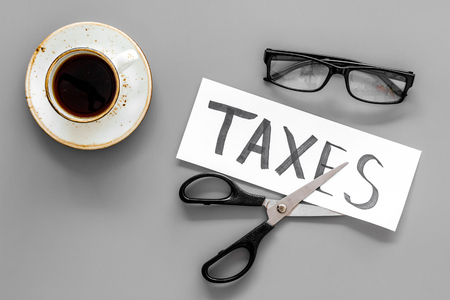 Tax reduce concept. Scissors and paper with word Taxes on grey background with coffee and glasses top view.