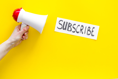 Subscribe template or mockup. Hand lettering subscribe near megaphone on yellow background top view space for text.