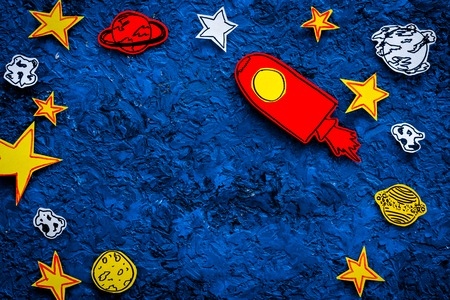 Space tourism concept. Drawn rocket or spaceship near stars, planets, asteroids on blue background top view. Stock Photo
