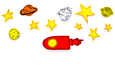 Space tourism concept. Drawn rocket or spaceship near stars, planets, asteroids on white background top view.