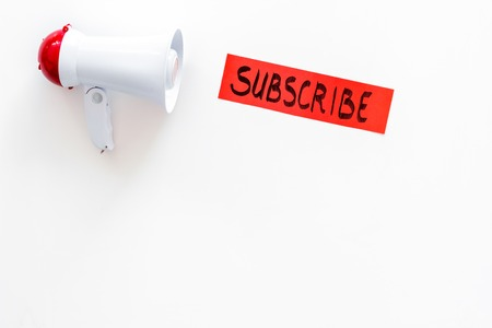 Subscribe template or mockup. Hand lettering subscribe near megaphone on white background top view.