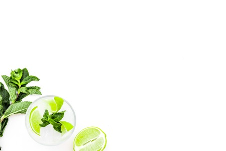 Refreshing mojito cocktail. Slices of lime, mint, glass with ice cubes on white background top view.