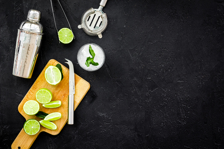 Make mojito cocktail with lime and mint. Shaker, strainer, glass near slices of lime on cutting board on black background top view. Stock Photo