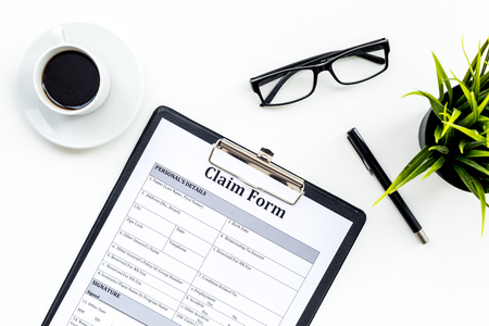 Claim form to fill out on white desk top view. Stock Photo