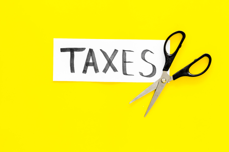 Cut taxes concept. Scissors cut paper with word Taxes on yellow background top view. 免版税图像