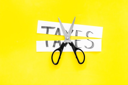 Cut taxes concept. Scissors cut paper with word Taxes on yellow background top view. 写真素材 - 102883139