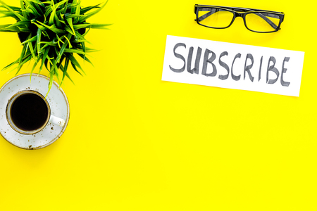 Email subscribe concept. Hand lettering subscribe on work desk with plant, glasses, cup of coffee on yellow background top view.