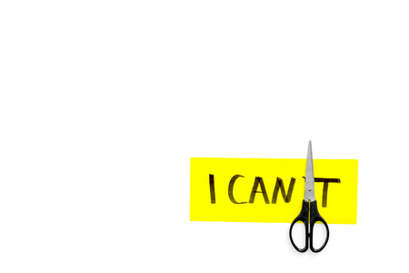 I can concept. Motivate yourself, believe in yourself. Scissors cut the letter t of written word I cant. White background top view. Banco de Imagens