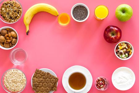 Ideas of healthy hearty breakfast for sportsmen. Fruits, oatmeal, yogurt, nuts, crispbreads, chia on pink background top view.