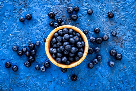 Fresh recently picked blueberries in bowl on blue background top view.